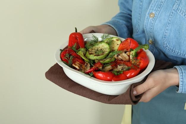 Vrouw houdt gegrilde groenten op beige