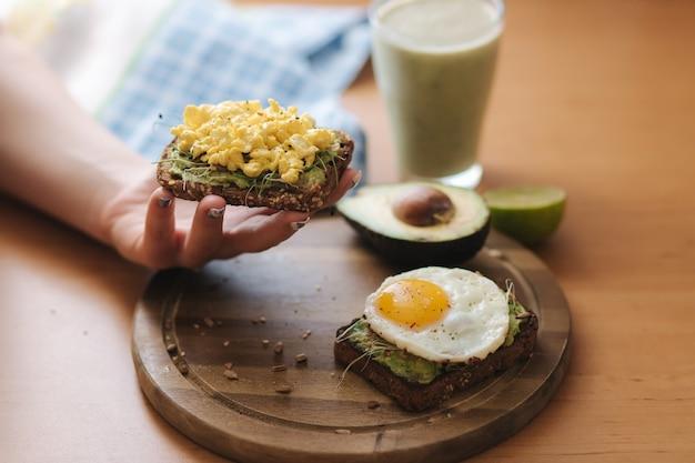 Vrouw houdt geroosterde sandwich. ei op avocado sandwich met volkoren brood op houten bord. smoothie met spinazie
