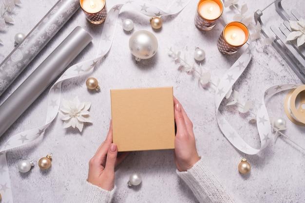 Vrouw houdt geschenkdoos vast tussen zilverachtige en witte sieraden voorbereiding op kerstmis en nieuwjaar mockup