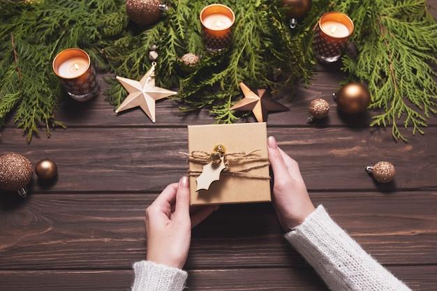 Vrouw houdt geschenkdoos versierd met touw en een houten label. kerstcompositie in bruin.