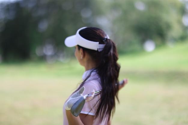 Vrouw houdt golfclub in haar handen en kijkt in de verte