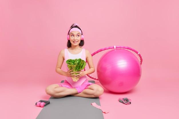 Vrouw houdt groene salade zit gekruiste benen op karemat houdt zich aan dieet leidt gezonde levensstijl heeft training gebruikt sportaccessoires