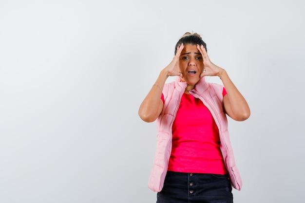 Vrouw houdt hand boven hoofd in t-shirt, vest en kijkt weemoedig