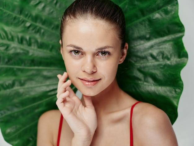 Vrouw houdt hand in de buurt van gezicht naakte schouder aantrekkelijk uiterlijk groen blad op achtergrond