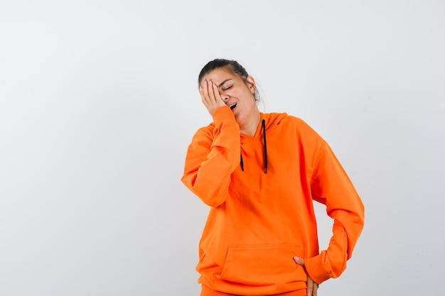 Vrouw houdt hand op gezicht in oranje hoodie en ziet er gelukkig uit