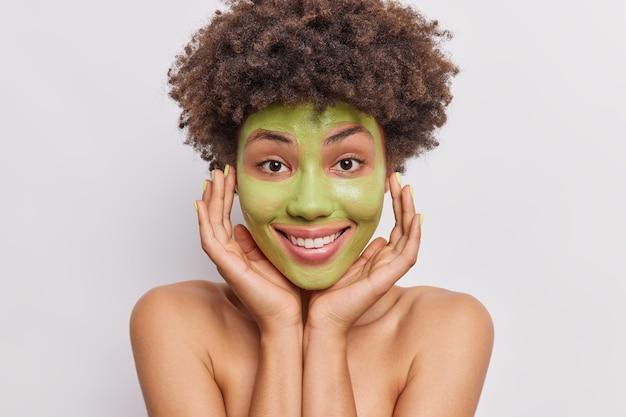 Vrouw houdt hand op gezicht past groen komkommermasker toe voor huidverzorgende poses topless op wit