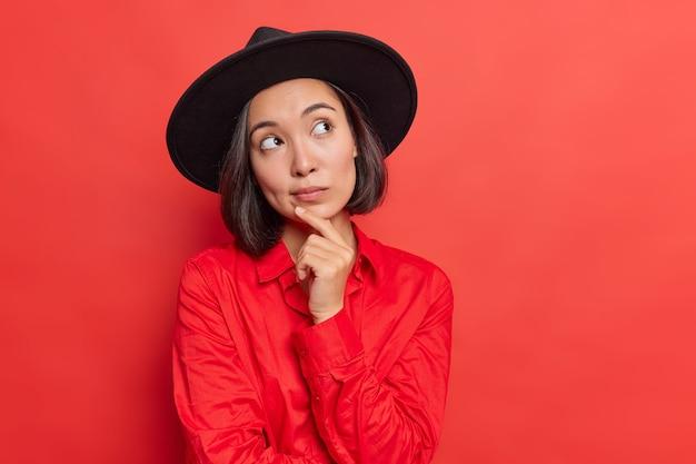 Vrouw houdt hand op kin diep in gedachten denkt dat iets een modieuze zwarte hoed draagt shirt poseert op rood