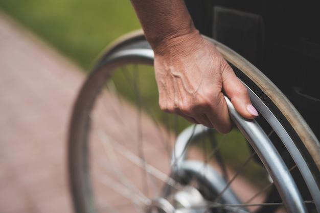 Vrouw houdt handen achter de wielen van de rolstoel