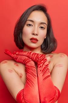 Vrouw houdt handen bij elkaar draagt rode lippenstift lange handschoenen poseert binnen heeft een verleidelijke uitdrukking