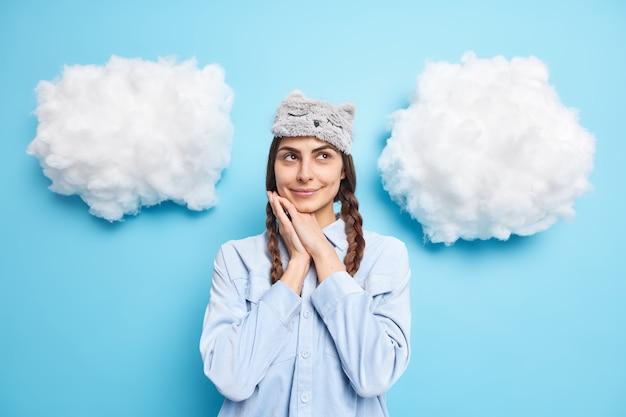 Vrouw houdt handen in de buurt van gezicht geconcentreerd boven diep in gedachten is draagt casual huiskleding poses tegen blauw