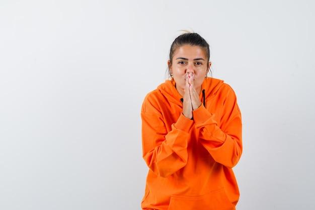 Vrouw houdt handen in gebedsgebaar in oranje hoodie en ziet er hoopvol uit