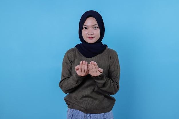 Vrouw houdt handen in gebedsgebaar, vraagt allah om een goede gezondheid, gelooft in welzijn heeft hoofd gesluierd