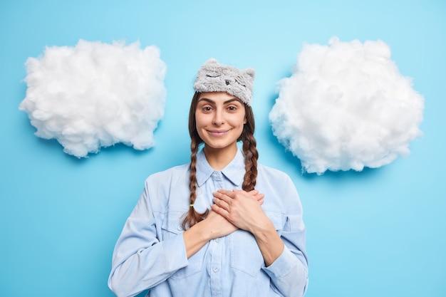 Vrouw houdt handen op borst glimlacht zorgeloos drukt dankbaarheid uit bedankt voor lof draagt blinddoek en shirt geïsoleerd op blauw