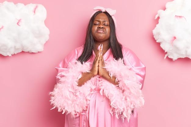 Vrouw houdt handpalmen bij elkaar in gebedsgebaar sluit ogen draagt kamerjas en hoofdband heeft hoop op beter geïsoleerd op roze