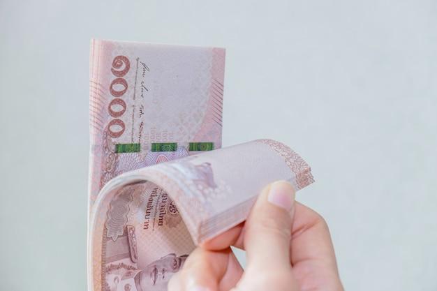 Vrouw houdt het bankbiljetgeld van thailand met grijze muur