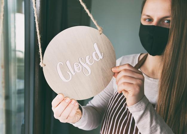 Vrouw houdt het houten bord vast met de tekst: closed