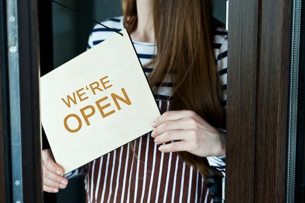 Vrouw houdt het houten bord vast met de tekst: we zijn open
