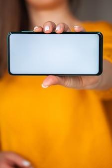 Vrouw houdt het schermmodel van de mobiele telefoon in handen in oranje trui