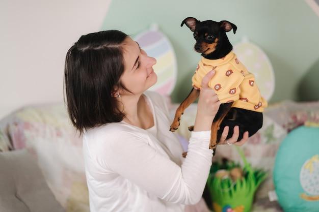 Vrouw houdt hondje in handen gelukkig vrouwelijk spel met schattig huisdier
