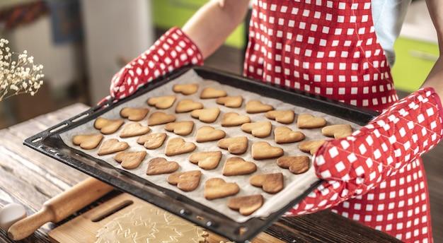 Vrouw houdt in haar handen een bakplaat met heerlijke zelfgemaakte koekjes in de vorm van een hart