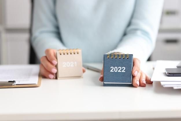 Vrouw houdt kalender vast voor 2021 en 2022 terwijl ze aan het bureau zit. jaar veranderen en samenvatten en plannen van bedrijfstakenconcept