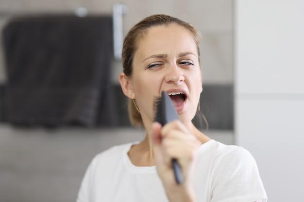 Vrouw houdt kam in haar handen en zingt voor spiegel.