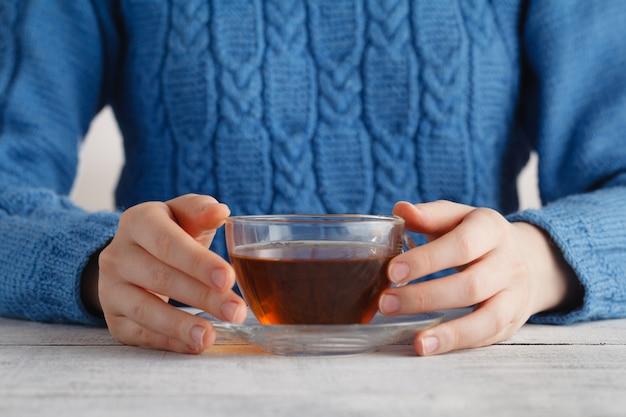 Vrouw houdt kopje thee in handen