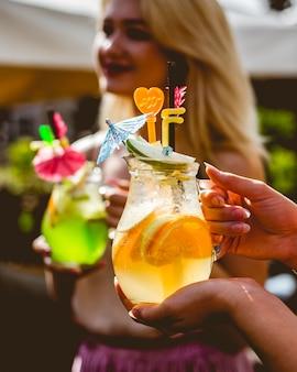 Vrouw houdt kruik citrus limonade oranje citroen appel ijs zijaanzicht