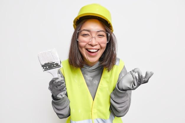 Vrouw houdt kwast vast en verbouwt huis draagt veiligheidsuitrusting en uniform lacht vrolijk