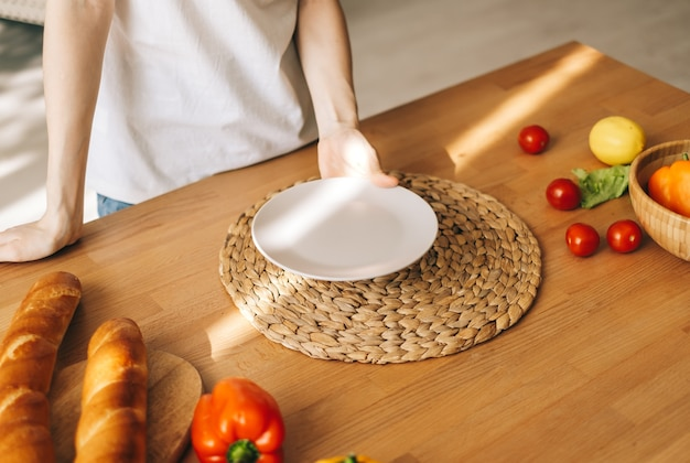 Vrouw houdt lege witte plaat op de houten tafel in de keuken