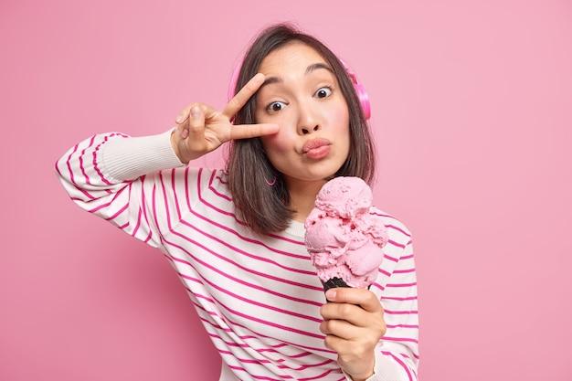 Vrouw houdt lippen gevouwen maakt vredesgebaar boven oog eet heerlijk ijs heeft zoetekauw dwazen rond draagt draadloze koptelefoon luistert naar muziek gekleed in gestreepte trui.