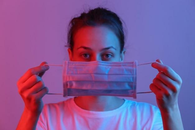 Vrouw houdt medisch masker voor haar gezicht in rood blauw neonlicht