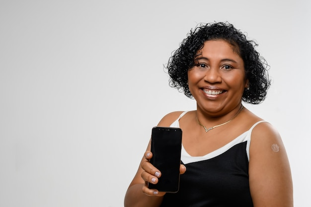 Vrouw houdt mobiele telefoon vast en lacht zonder gezichtsmasker nadat ze is ingeënt ruimte voor tekst