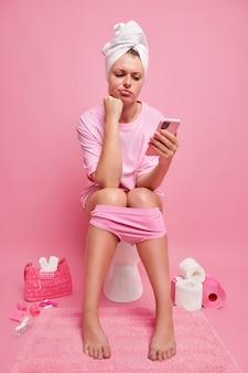 Vrouw houdt mobiele telefoon vast surft sociale netwerken verslaafd aan moderne technologieën draagt badhanddoek t-shirt slipje poseert in de badkamer alleen stuurt sms-berichten