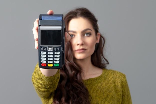 Vrouw houdt moderne bankbetalingsterminal om creditcardbetalingen te verwerven