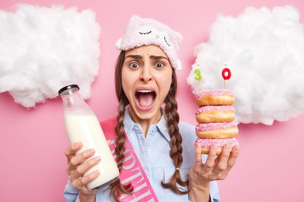 Vrouw houdt mond open viert verjaardag alleen roept luid poses met heerlijke geglazuurde donuts en melk geïsoleerd op roze