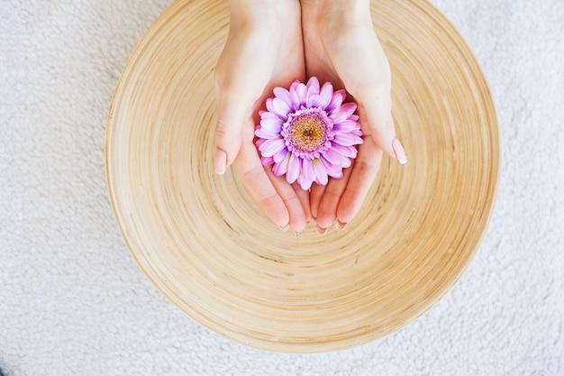 Vrouw houdt mooie bloem in haar handen