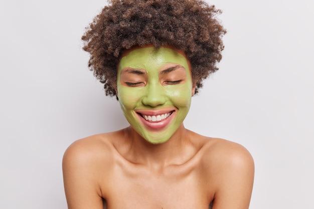 Vrouw houdt ogen gesloten glimlacht breed past groen voedend masker op gezicht ondergaat huidverzorgingsprocedures staat met blote schouders op wit