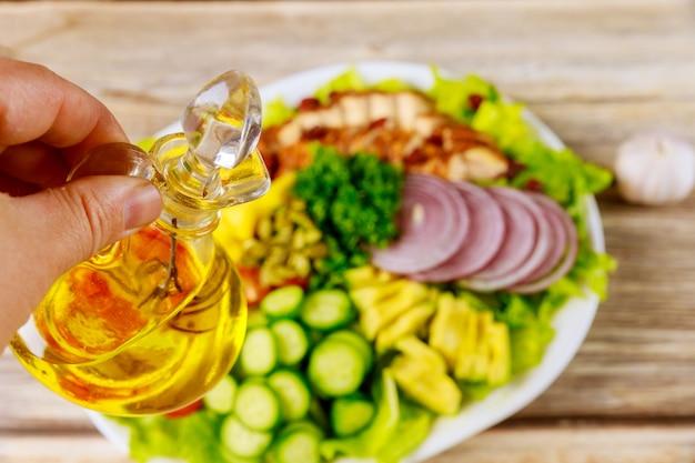 Vrouw houdt olijfolie voor groente salade