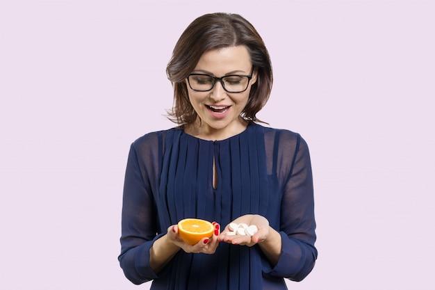 Vrouw houdt oranje en synthetische vitamine c