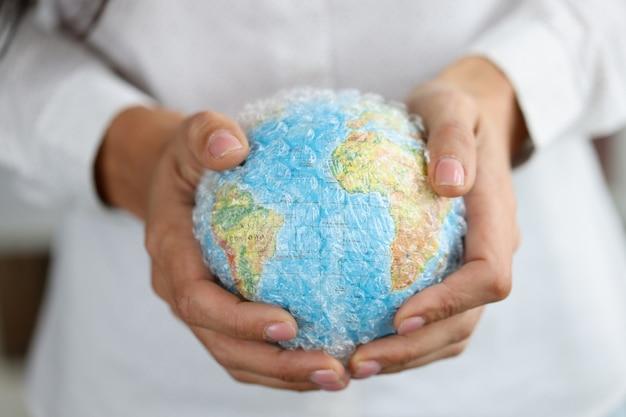Vrouw houdt overdekte wereldbol vast met milieuproblemen en gevolgen van de opwarming van de aarde