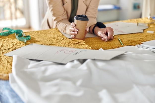 Vrouw houdt papieren beker leunend op snijtafel met stof en gereedschap in werkplaats