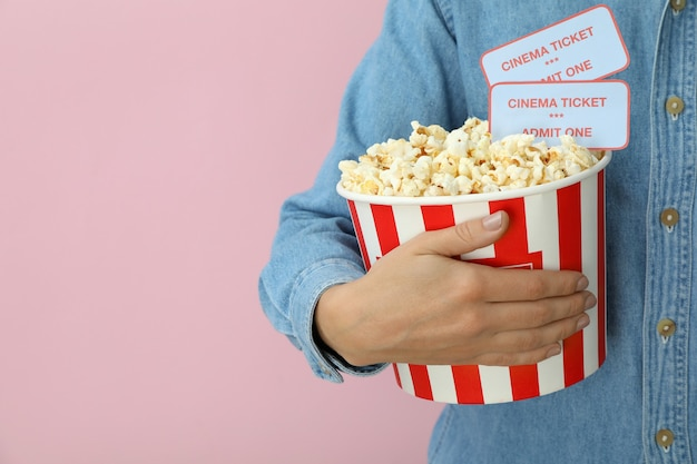 Vrouw houdt papieren beker met popcorn en kaartjes op roze achtergrond.