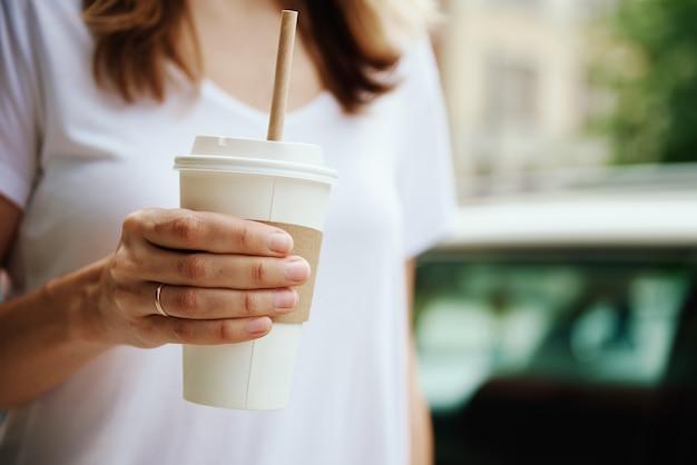 Vrouw houdt papieren koffiekopje vast op straat in de stad