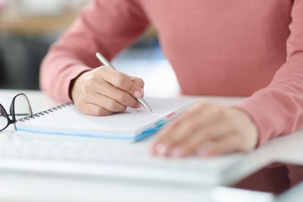 Vrouw houdt pen in haar handen en maakt aantekeningen in dagboek. plannen en instellen van dagelijkse taken concept
