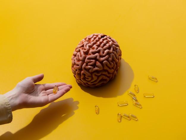 Vrouw houdt pillen in de buurt van hersenen op geel oppervlak