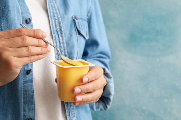 Vrouw houdt plastic beker zure room yoghurt en lepel tegen blauwe muur