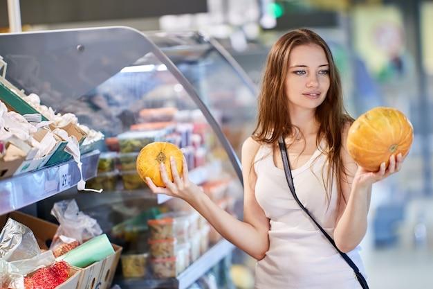 Vrouw houdt pompoenen vast in supermarkt tijdens het winkelen