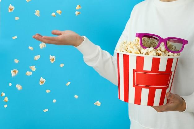 Vrouw houdt popcorn met 3d-bril op blauwe achtergrond met vliegende popcorn.