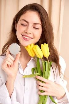 Vrouw houdt pot met schoonheidsproduct in haar hand met gele tulpen en beige gordijnachtergrond